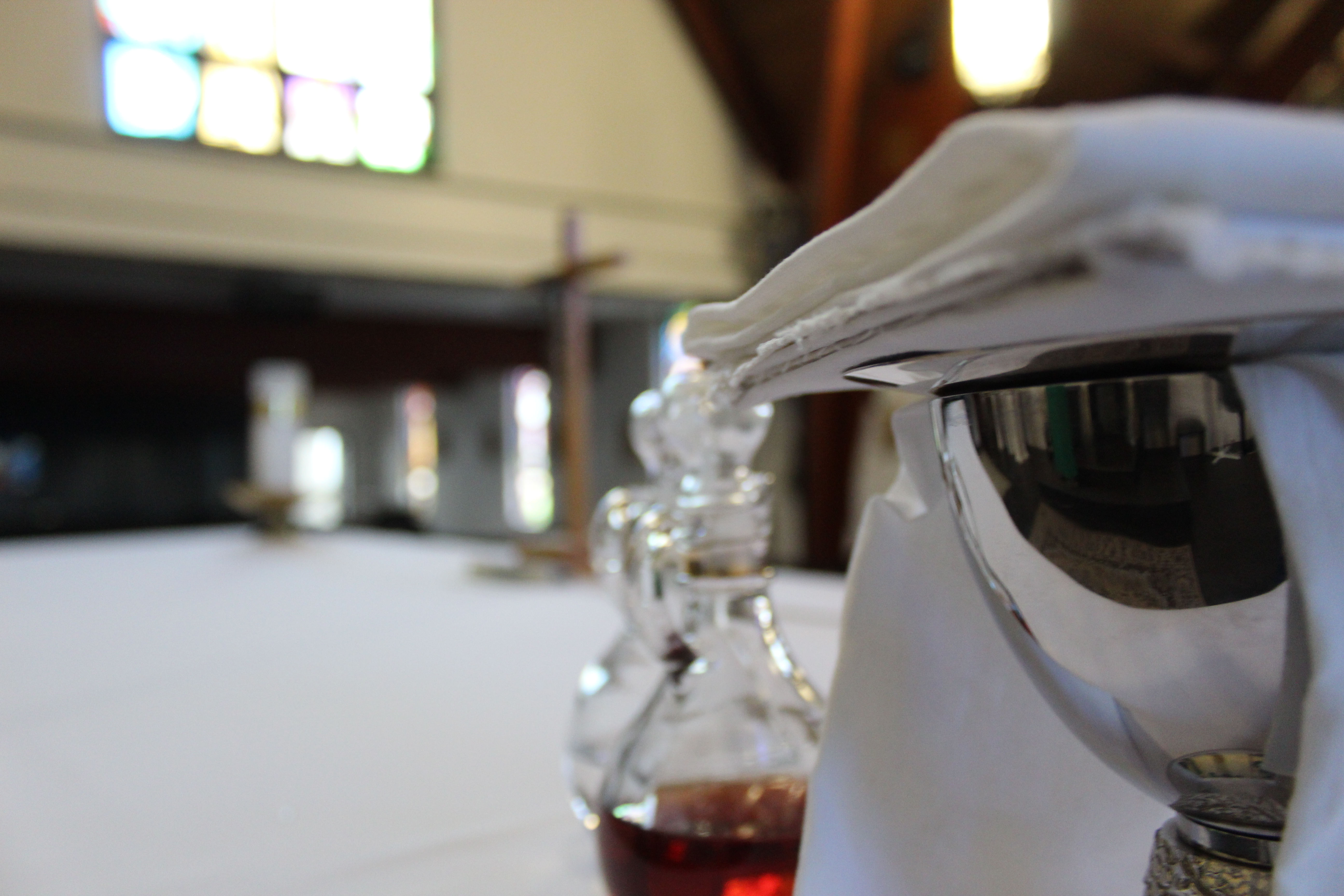 Side angle photo of a silver chalice and cruets (with water and wine in them) on the altar.